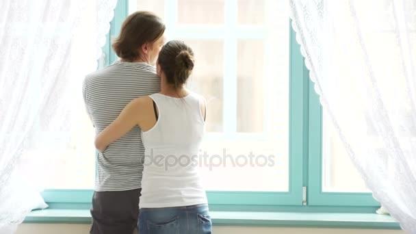 Šťastné rodiny idyly objímání jejich malé děti nedaleko světlé okno