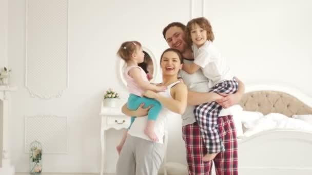 Mladá rodina s dětmi v ložnici
