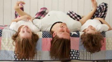 Mladý otec a jeho děti si hrají na posteli