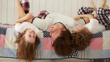 Mladá rodina - otec a jeho děti si hrají na posteli