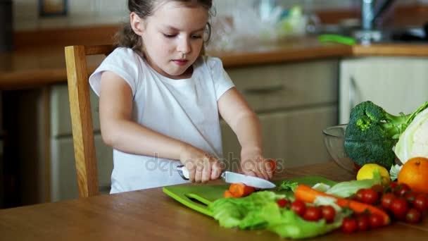 Dívka v kuchyni rozřezání mrkev.