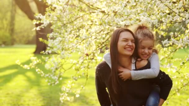 glückliche Familie - junge Mutter und Tochter im Blumengarten.