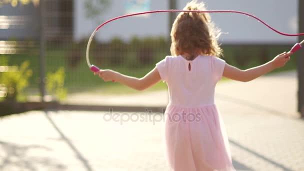 Porträt eines lockigen hübschen Mädchens mit Seil in einem zartrosa Sommerkleid.