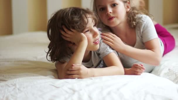 Malý bratr a sestra ležící na posteli.