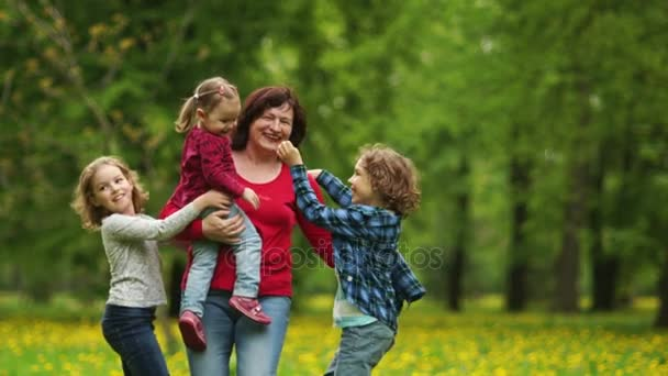 Grandmother with grandchildren walking in the Park. Children run to the grandmother and embrace her. Continuity of generations, family love, fun weekend, active old age