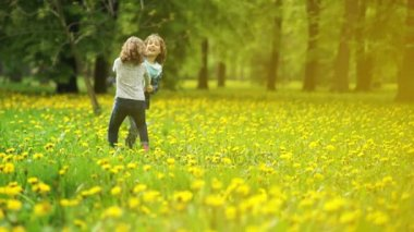 Cute girl and boy 9-10 years old with curly hair spinning in the park on the glade of dandelions