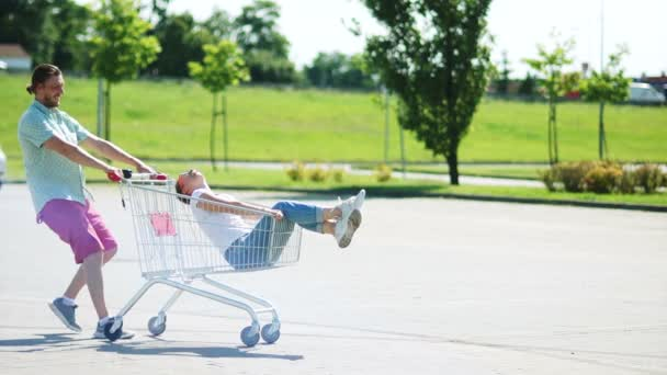 Shopping cart on parking. A couple of newlyweds ride in a shopping basket near a supermarket. Fun, joke, joy, sense of humor, family love, family everyday life
