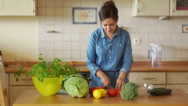 Vonzó fiatal nő állt konyhaasztal és a zöldség vágás. Egészséges életmód, bio élelmiszerek, a vegán étrend
