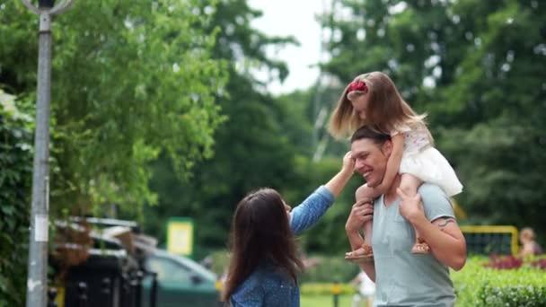 Šťastná rodina. Otec drží svou dceru na svých bedrech. Nakláněl dívku k mámě a šťastně, směje se. Vlasy krásně vlaje ve větru.