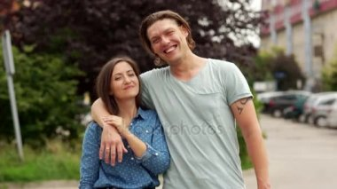 Lovely young couple. The man laughs cheerfully. The girl looks intently into the lens. Close-up portrait.