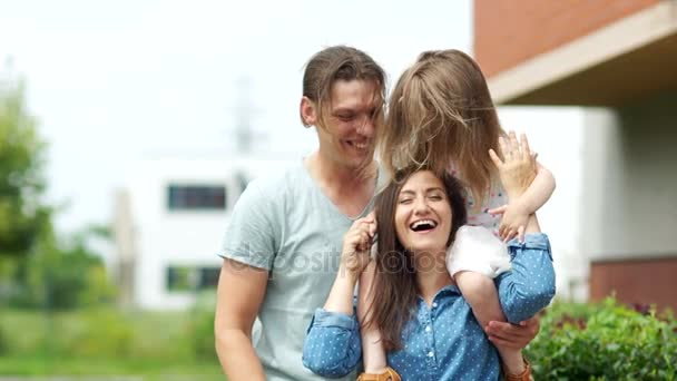 Young parents and their little daughter. Father hugs his girls. Family idyll.
