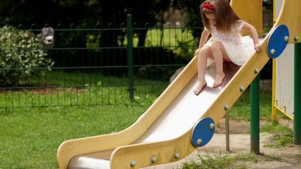 Draußen Portrait von niedlichen kleinen Mädchen spielen auf der Kinderrutsche auf dem Spielplatz im Sommer sonnigen Tag.