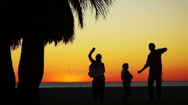 Tramonto sulloceano. Danza sagome di genitori e figli. Tre danze, il quarto corre verso