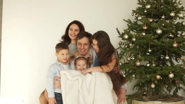 Rodinný portrét rodičů a tři děti v blízkosti vánoční stromeček. Veselé Vánoce a nový rok. Dítě je zabalené v dece