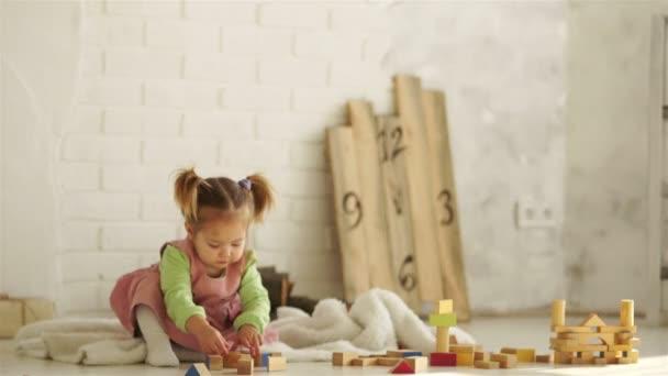 Krásné dítě si hraje na podlaze s dřevěnými kostkami. Vzdělávací hračky. Předškolní vzdělání. Mateřské školy