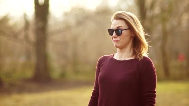 Blondýna v pozadí jaro park. Dívka nešťastný, její tvář má emoce, pohrdání a překvapení. Ona nosí sluneční brýle na ní, její levé obočí rozhořčeně zvedl