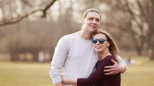 Porträt eines reiferen Paares, das im zeitigen Frühling im Park Urlaub macht. Ein Mann und eine Frau umarmen sich und blicken gelassen in die Kamera. Valentinstag. Zeitlupe