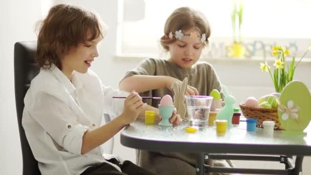 Gyerekek festék húsvéti tojás otthon. Húsvéti hagyományok