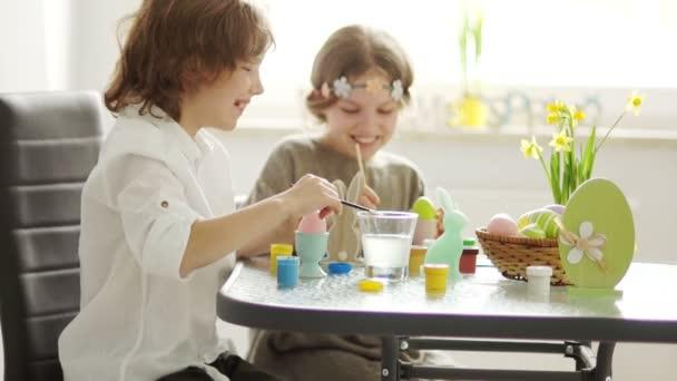 Testvérpár festék húsvéti tojás otthon a konyhában. Koncentrálva. Ecsetek és festékek, gyermek kreativitás