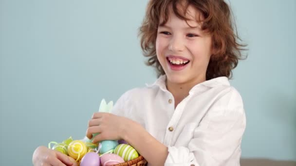 Klaus ap portrait of a curly red-haired boy with a basket of Easter eggs in his hands. Happy easter