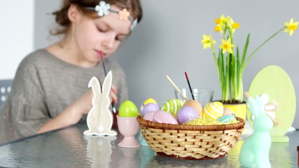 Das schöne Mädchen malt die Figur des Osterhasen. Gibt es Farben auf dem Tisch, ein Korb mit Ostereiern und einen Strauß Narzissen