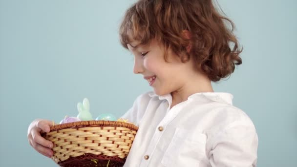 Boy with Easter basket. Teenager shows on his outstretched hand a gently blue Easter egg