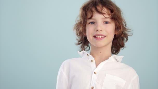 Bílé tričko na teenager. Krásné kavkazské usmívající se dítě, na světle modrém pozadí. Pojem dětství, módní nebo návrh reklamy