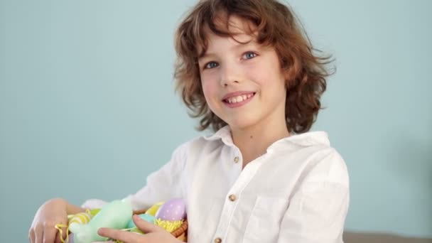 A child holds a Easter bunny and a set of decorative Easter eggs. The boy laughs cheerfully. Slow Motion