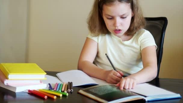 Školačka dělá domácí úkoly. Na stole jsou učebnice, sešity a tužky. Zpátky do školy. Příprava na výuku. Domácí úkol. Den znalostí