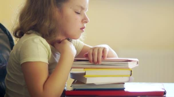 Smutná dívka sedí u stolu s hromadou knih. Problémy školního vzdělávání. Zpátky do školy