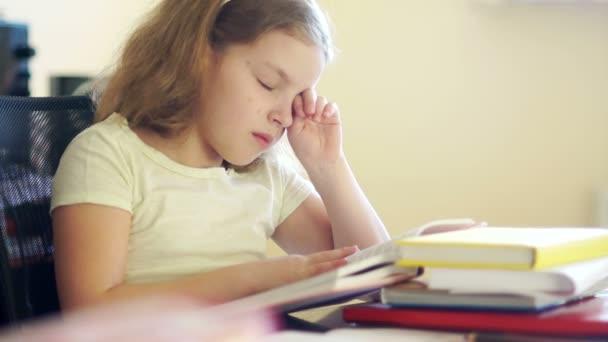 Szomorú lány egy halom könyvet ül az asztalnál. Ő dörzsöli a szemét, és azt akarja, hogy aludni. Problémák az iskolai oktatás. Vissza az iskolába