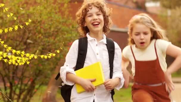 Bátyja és húga, iskolás, fiú és lány ölelés, egy virágzó Tavaszi fa a háttérben. A fiú kezében van egy könyv, mögötte egy táska. Nap a tudás. Vissza az iskolába