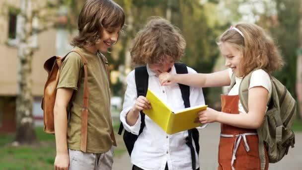 Tři studenti se na knihu a vesele smát. Den dětí. Zpátky do školy