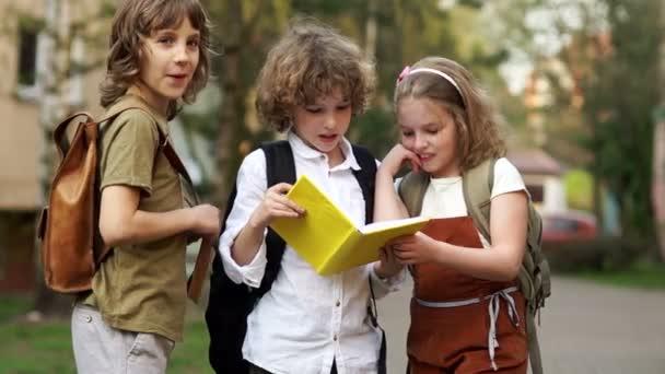 Tři studenti se na knihu a vesele smát. Chlapci se lišácky. Den dětí. Zpátky do školy