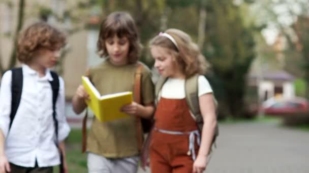 Dospívající děti nadšeně číst knihu na cestě do školy. Zpátky do školy. Šťastné dětství