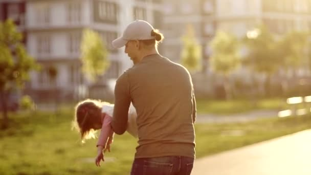 The young father turns around and tosses his little daughter. The girl laughs cheerfully. A man is wearing a baseball cap. Happy childhood. Fathers Day. Circling the child. Childrens Day
