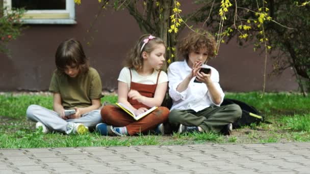 The girl is reading a book, the boys are playing games in smartphones. The schoolgirl is upset, angry, bored. Internet addiction. Back to school