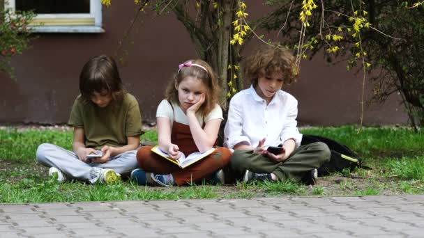 Students communicate in social networks using smartphones, the girl wants to show them the book they read. the boys are not interested. Leisure of schoolchildren, active leisure. Gambling addiction