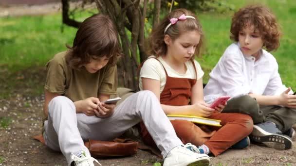 Zwei Jungen und ein Mädchen spielen auf dem Rasen Videospiele. Ein Mädchen bekommt ein Selfie. Internetsucht, soziale Netzwerke