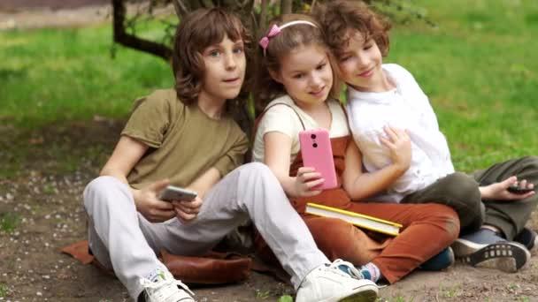 Studenti během školní přestávky sedět na trávě a focení. Dva chlapci a dívka, školy, přátel jsou fotografoval na fotoaparát smartphone. Zpátky do školy