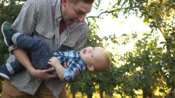 Mladý otec a jeho malý syn se baví na zahradě proti zapadajícímu slunci. Multi Generation Family, Den otců