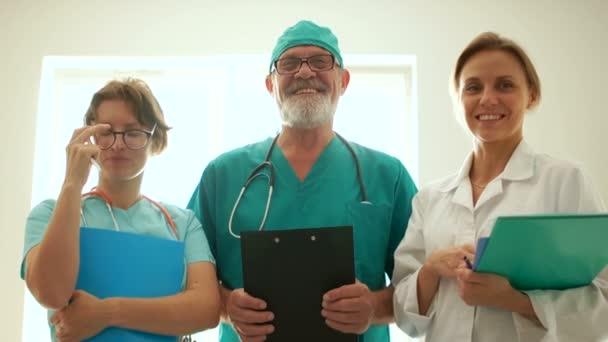 Chefarzt der Klinik und zwei junge Internisten. Ärztliche Karriere, medizinischer Hintergrund. Drei Ärzte lächeln nah Porträt