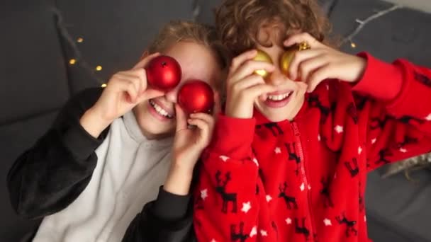 Pair of happy children in pajamas have fun in the bedroom, playing with New Years balls. Christmas preparations