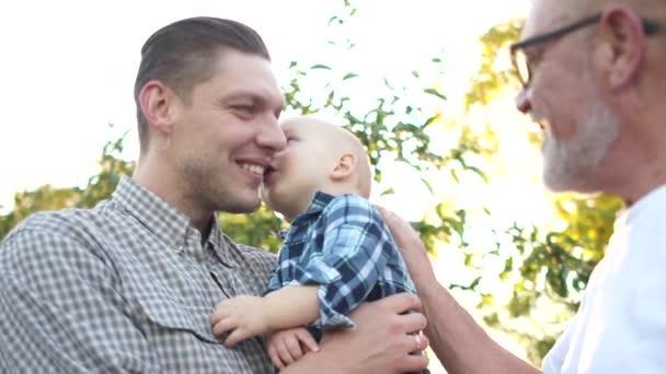 Malý syn líbá svého otce. Tři generace stejné rodiny se při západu slunce baví v jablečném sadu. Dědeček, syn a vnuk se smějí