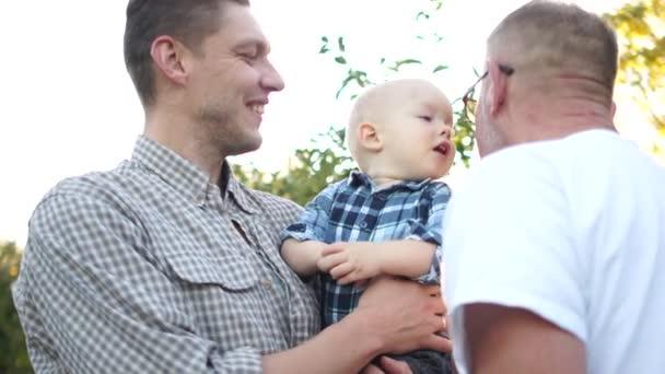 A kis unoka megcsókolja nagyapát. Ugyanannak a családnak három generációja szórakozik az almás gyümölcsösben naplementekor. Nagyapa, fia és unokája nevetnek.