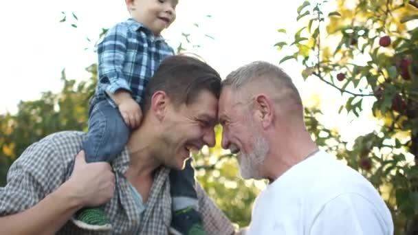 Šťastná rodina, tři generace mužů stejné rodiny. Dítě batole, jeho otec a dědeček se baví v letní zahradě