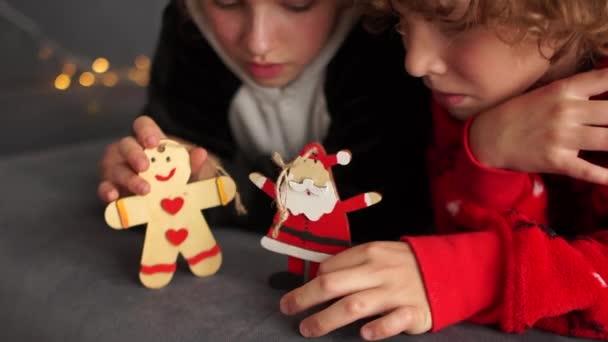 Šťastné děti ve vánočním pyžamu čeká na vánoční zázrak hrát s dřevěnými panenkami perník a Santa