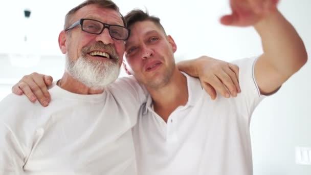 Šťastné dvě generace mužů starý otec smích objímající malého syna, starší táta objímají dospělého muže baví. Den otců, věkový rozdíl