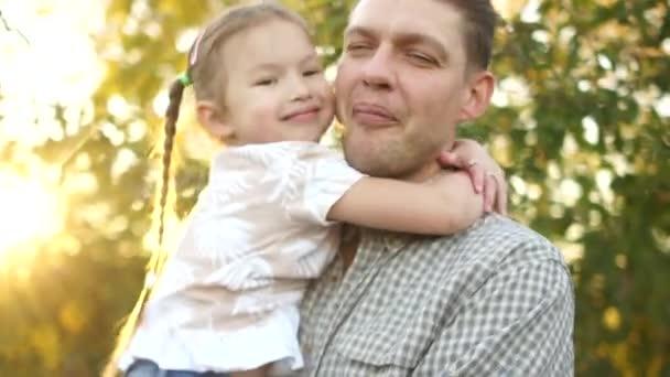 Šťastná rodina, otec a dcera v jablečném sadu při západu slunce, sluneční svit. Den otců