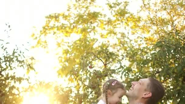 Der junge Mann wirft ein fünfjähriges Mädchen zur Welt. das Kind lacht und ist glücklich. glückliche Familie, Vater und Tochter im herbstlichen Apfelgarten, Sonnenuntergang